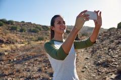 Jeune fille prenant le selfie sur le flanc de coteau Photos libres de droits