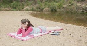 Jeune fille prenant un bain de soleil sur une plage de rivière portant l'usage coloré de bain banque de vidéos