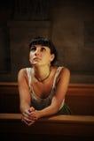 Jeune fille priant dans l'église Photo libre de droits
