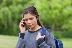 Jeune fille réfléchie à l'aide de son téléphone portable Photos stock