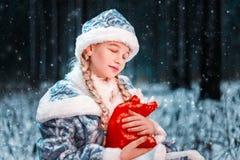 Jeune fille réfléchie et romantique de neige peu de fille dans une forêt fabuleuse d'hiver tient dans des ses mains un sac avec d photographie stock