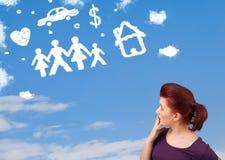 Jeune fille rêvassant avec des nuages de famille et de ménage Photographie stock libre de droits