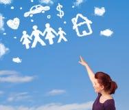 Jeune fille rêvassant avec des nuages de famille et de ménage Photo stock