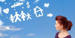 Jeune fille rêvassant avec des nuages de famille et de ménage Photos stock