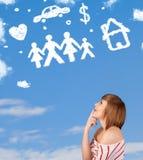 Jeune fille rêvassant avec des nuages de famille et de ménage Photographie stock
