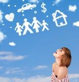 Jeune fille rêvassant avec des nuages de famille et de ménage Image libre de droits