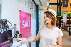 Jeune fille rêveuse regardant la fenêtre de boutique avec des chaussures et des sacs dans le centre commercial Client ventes Cent Images libres de droits