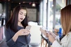 Jeune fille regardant à son téléphone du ` s d'ami et passionnant se sentant Images stock