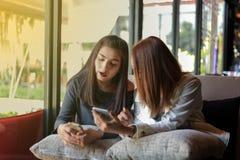 Jeune fille regardant à son téléphone du ` s d'ami et passionnant se sentant Photographie stock