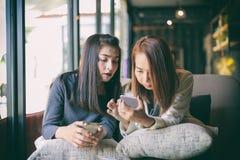 Jeune fille regardant à son téléphone du ` s d'ami et passionnant se sentant Photo stock