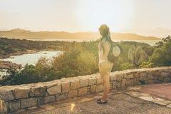 Jeune fille regardant le lever de soleil dans le capo Ferro sur Costa Smeralda image libre de droits