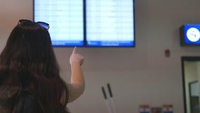 Jeune fille regardant le programme de vol l'aéroport Femme dirigeant quelque chose à l'écran de panneau d'horaire Vérifie la lign clips vidéos