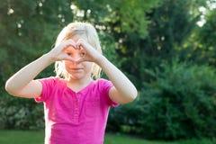 Jeune fille regardant par des mains de coeur Photos libres de droits