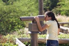 Jeune fille regardant par le télescope Photographie stock libre de droits