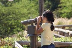 Jeune fille regardant par le télescope Image libre de droits
