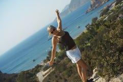 Jeune fille restant sur une falaise Photos libres de droits