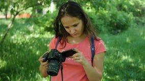 Jeune fille retenant un appareil-photo Pour poser pour l'appareil-photo Amusement à l'extérieur Images libres de droits