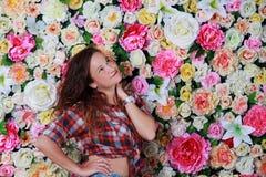 Jeune fille romantique de brune près de mur de fleur Images stock