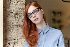 Jeune fille rousse attirante avec des verres et le stu bleu de chemise photos libres de droits
