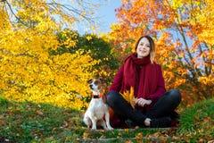 Jeune fille rousse dans des vêtements rouges se reposant sur l'escalier près du chien dans p Images stock