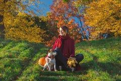 Jeune fille rousse dans des vêtements rouges se reposant sur l'escalier près du chien dans p Photos libres de droits