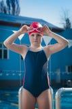 Jeune fille sérieuse apprenant à nager dans la piscine Photographie stock libre de droits