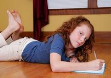 Jeune fille s'étendant sur l'écriture d'étage Photo libre de droits