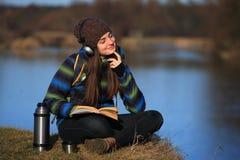 Jeune fille s'asseyant au sol et détendant avec le livre Photo libre de droits