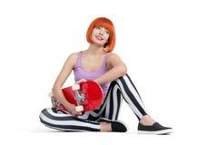 Jeune fille s'asseyant avec la plate-forme de planche à roulettes, d'isolement sur le fond blanc Photographie stock