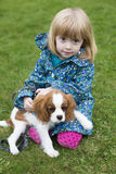 Jeune fille s'asseyant avec le Roi Charles Spaniel de chiot Image stock