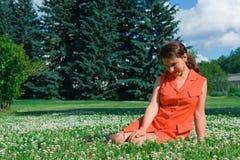 Jeune fille s'asseyant dans l'herbe Photos stock