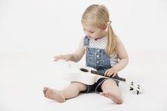 Jeune fille s'asseyant dans le studio, jouant une guitare Photographie stock libre de droits