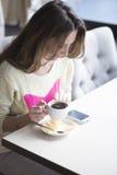 Jeune fille, s'asseyant dans un café avec la tasse de café Images libres de droits
