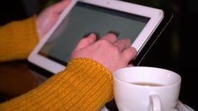 Jeune fille s'asseyant en café à la table et aux utilisations une tablette La fille met à jour les réseaux sociaux Remet le plan  banque de vidéos