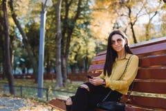 Jeune fille s'asseyant en parc avec le téléphone dans des ses mains Image libre de droits
