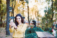 Jeune fille s'asseyant en parc avec le téléphone dans des ses mains Photo stock