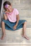 Jeune fille s'asseyant sur des marchepieds Photo stock