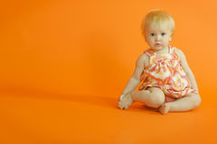 Jeune fille s'asseyant sur l'étage photos stock