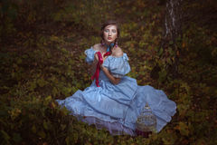 Jeune fille s'asseyant sur l'herbe photos stock