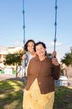 Jeune fille s'asseyant sur l'oscillation avec la grand-mère dedans Photographie stock libre de droits