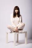 Jeune fille s'asseyant sur la petite table Image libre de droits