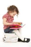 Jeune fille s'asseyant sur la pile de l'affichage de livres Image libre de droits
