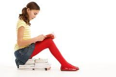 Jeune fille s'asseyant sur la pile de l'affichage de livres Photographie stock libre de droits