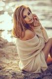 Jeune fille s'asseyant sur la plage après coucher du soleil à l'arrière-plan de mer Photo stock