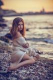 Jeune fille s'asseyant sur la plage après coucher du soleil à l'arrière-plan de mer Images libres de droits