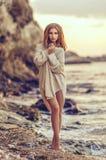 Jeune fille s'asseyant sur la plage après coucher du soleil à l'arrière-plan de mer Photographie stock libre de droits