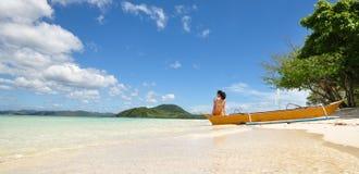 Jeune fille s'asseyant sur le bateau sur la plage Image libre de droits