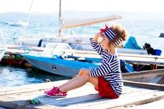 Jeune fille s'asseyant sur le dock Photo stock