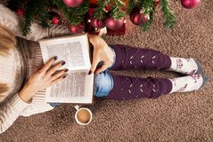 Jeune fille s'asseyant sur le livre de plancher et de lecture à côté de l'arbre de Noël et de la tasse de café Photos libres de droits
