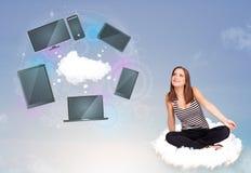 Jeune fille s'asseyant sur le nuage appréciant le service en réseau de nuage Photos libres de droits
